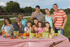 Multi-ethnic friends eating at picnic table - stock photo