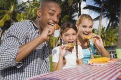 Mixed Race family eating at picnic table - stock photo