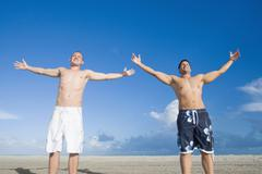 Multi-ethnic men with arms outstretched Stock Photos
