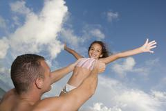 Father holding daughter in air Stock Photos