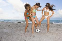 Multi-ethnic girls playing soccer at beach Stock Photos