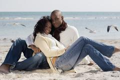 Multi-ethnic couple hugging at beach Stock Photos