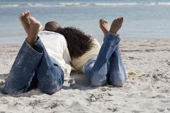 Multi-ethnic couple laying on beach Stock Photos