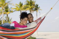 Hispanic couple laying in hammock - stock photo