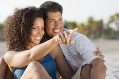 Hispanic couple hugging and pointing Stock Photos