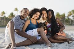 Multi-ethnic couples sitting on beach Stock Photos