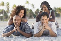 Multi-ethnic couples laying on beach - stock photo