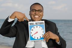 African businessman holding clock sign Stock Photos