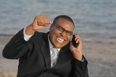 African businessman cheering on cell phone Stock Photos