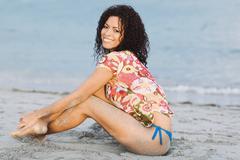 Hispanic woman sitting on beach Stock Photos