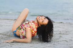Stock Photo of Hispanic woman laying on beach