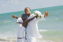 African bride and groom at beach - stock photo