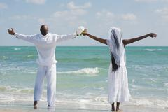 African bride and groom with arms outstretched Stock Photos