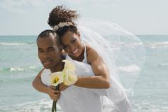 Multi-ethnic bride and groom hugging at beach Stock Photos