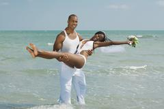 African groom carrying bride at beach Stock Photos