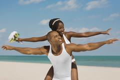 African bride and groom with arms outstretched at beach Stock Photos
