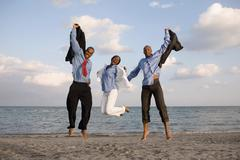 African businesspeople cheering at beach Stock Photos