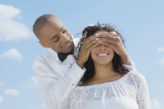 African groom covering bride's eyes Stock Photos