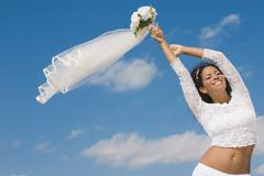 Hispanic bride holding bouquet over head Stock Photos