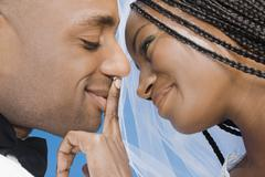 African bride touching groom's lips Stock Photos