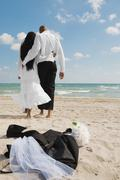 African bride and groom walking on beach Stock Photos
