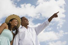 Multi-ethnic couple pointing and laughing Stock Photos