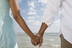 Multi-ethnic couple holding hands Stock Photos