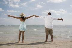 African couple with arms outstretched at beach Stock Photos