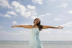African woman with arms outstretched at beach Stock Photos