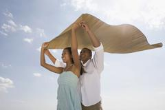 Stock Photo of African couple holding mat in wind