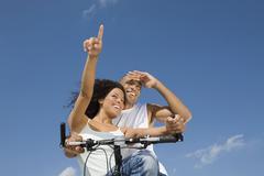 Multi-ethnic couple sitting on bicycle Stock Photos