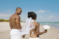 African bride and groom holding hands at beach Stock Photos