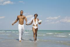 African bride and groom running in ocean surf Stock Photos