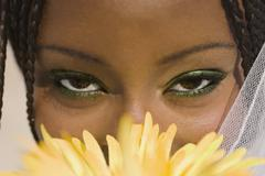African woman with flower in front of face Stock Photos
