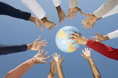 Multi-ethnic hands reaching for globe ball Stock Photos