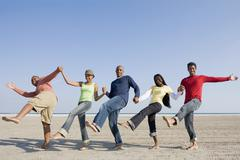Multi-ethnic friends holding hands and kicking - stock photo