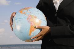 African businesswoman holding globe Stock Photos