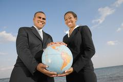 African businesspeople holding globe - stock photo
