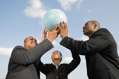 Stock Photo of African businesspeople holding up globe