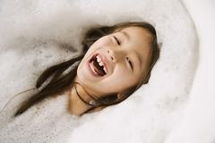 Asian girl laughing in bubble bath Stock Photos
