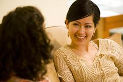 Asian woman talking to friend - stock photo