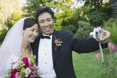 Asian newlyweds taking own photograph Stock Photos