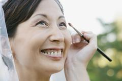 Asian bride having makeup applied Stock Photos