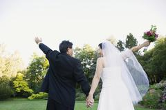 Asian newlyweds with arms raised Stock Photos
