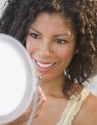 African woman applying lip gloss Stock Photos