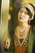 Asian woman looking out window Stock Photos