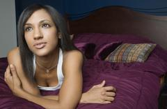 Mixed Race woman laying on bed - stock photo