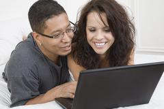 Hispanic couple looking at laptop - stock photo