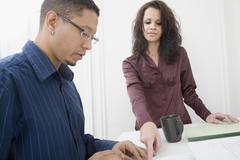 Hispanic couple looking at paperwork - stock photo