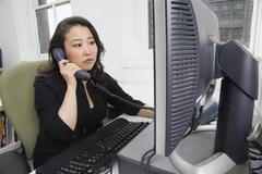 Asian businesswoman talking on telephone Stock Photos